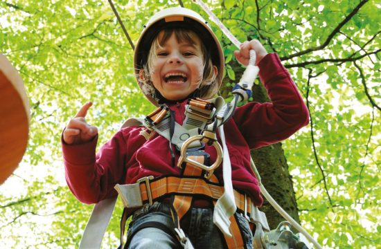 Bambina sul percorso a corde alte